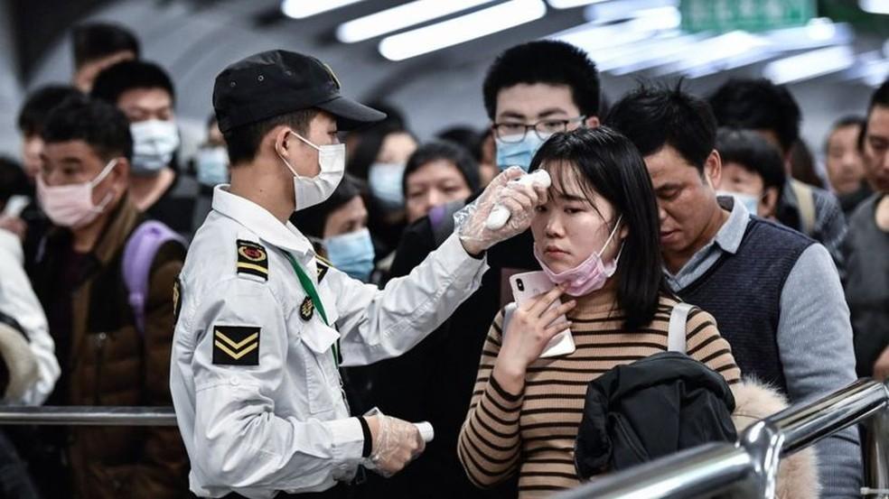Pessoas passam por teste de infravermelho em aeroporto, a fim de detectar sintomas causados por Coronavírus. — Foto: Getty Images